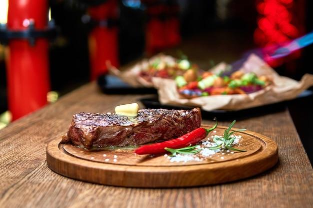 Weicher fokus. entrecote beef gegrilltes steakfleisch mit feuerflammen auf holzbrett mit rosmarinzweig, pfeffer und salz. meisterkoch, der köstlichen grillgrill kocht. butter schmelzen