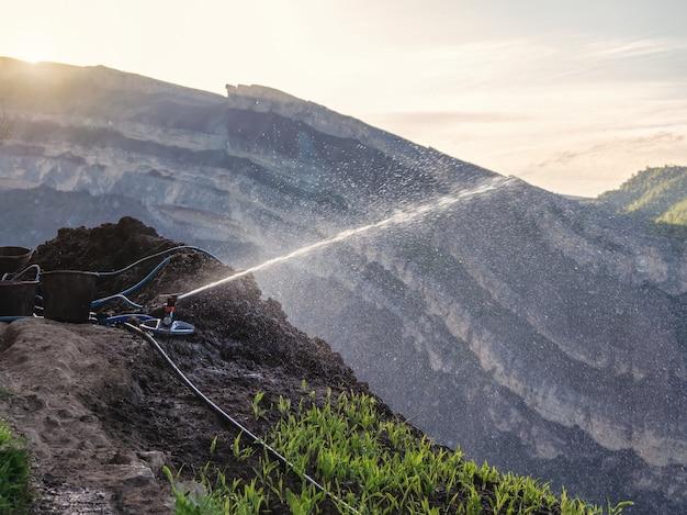 Weicher fokus. sprinkler, der wasser auf frühlingsbergrasen sprüht. produktion von bergpflanzen.