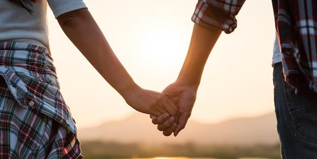 Weicher fokus von zwei partnern, die bei sonnenuntergang die hand vor dem berg halten