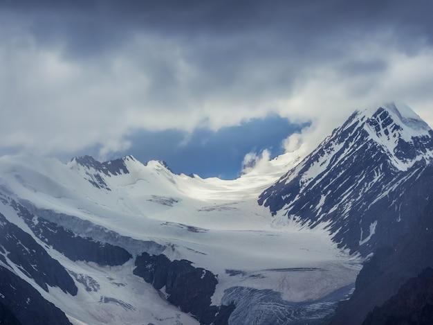 Weicher fokus. wunderbare minimalistische landschaft mit großen schneebedeckten berggipfeln über niedrigen wolken. atmosphärischer minimalismus mit großen schneeberggipfeln, dunklem gletscher im dramatischen himmel.