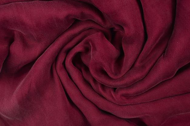 Weicher glatter burgunderfarbener seidenstoffhintergrund. stoff textur.