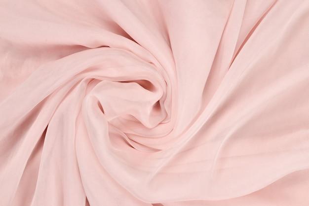 Weicher glatter rosa seidenstoffhintergrund. stoffstruktur.