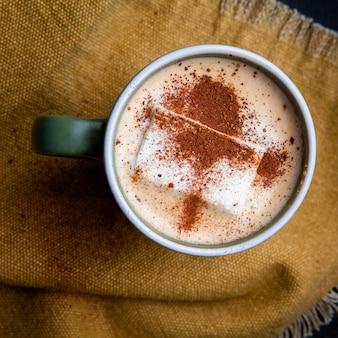 Weicher milchiger kaffee in einer tasse lag flach auf einem stück sack