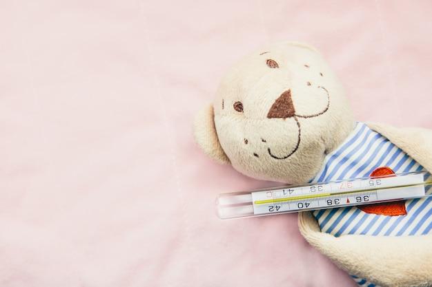 Weicher spielzeugbär mit thermometer auf rosafarbenem backgroun. gesundes kind