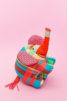 Weicher spielzeugelefant, helles mehrfarbiges textilspielzeug auf rosa papierhintergrund mit kopienraum. handgemachte sache für kind oder dekor. hochformat.