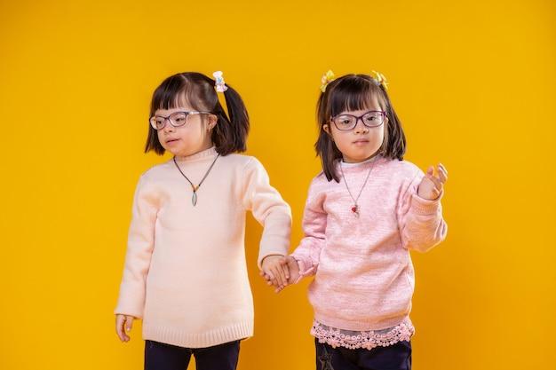 Weicher warmer pullover. zwei junge schwester, die zusammen stehen und hände halten und klare brille für schlechte sicht tragen