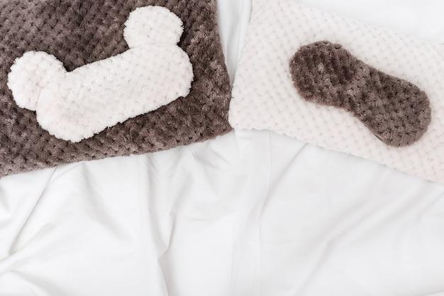 Weiches, flauschiges kissen und schlafmaske auf weißem, zerknittertem laken