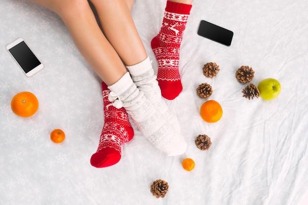 Weiches foto von frau und mann auf dem bett mit telefon und früchten, draufsicht. weibliche und männliche beine des paares in warmen wollsocken. weihnachten, liebe, lifestyle-konzept