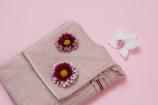 Weiches frotteetuch mit roten gerbera und weißen orchideenblütenknospen auf rosa hintergrund. ansicht von oben.