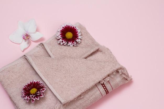 Weiches frotteetuch mit roter chrysantheme und weißen orchideenblütenknospen auf rosa hintergrund. ansicht von oben.