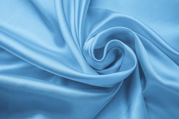 Weiches gewelltes pastellmaterial, blau glänzende textur des textils. satinfalten, wellenmuster. seidiger hintergrund mit kurven, luxusmode. gefaltetes tuch, tapete.