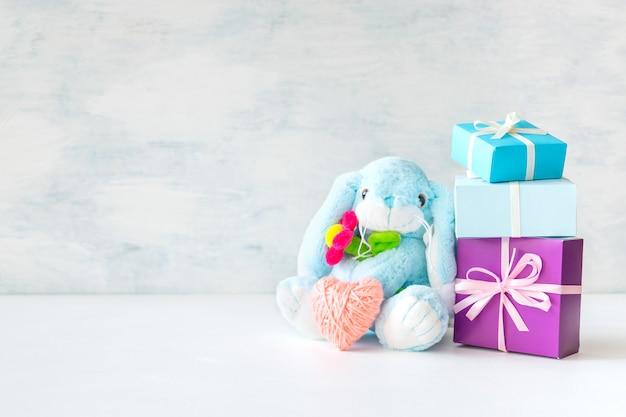 Weiches häschen des netten spielzeugs mit blume, rosa herzen, geschenkboxen und seifenblasen
