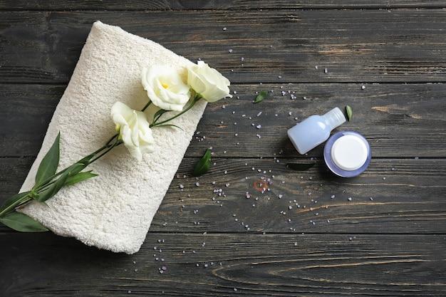 Weiches handtuch mit kosmetik und blumen auf holztisch