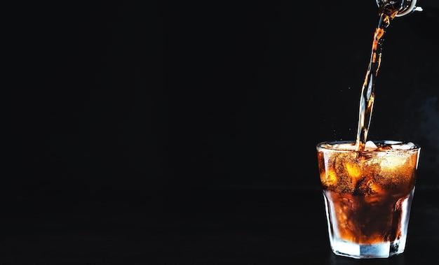 Weiches kohlensäurehaltiges cola-getränk wird in ein glas eis gegossen