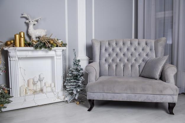 Weiches samtgraues sofa mit kamin und kleinem weihnachtsbaum oder neujahrsbaum im grauen wohnzimmer.
