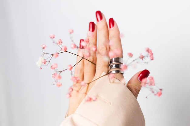 Weiches sanftes foto der frauenhand mit roter maniküre des großen rings halten niedliche kleine rosa getrocknete blumen auf weiß.