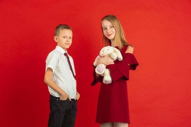 Weichheit geben. valentinstagfeier, glückliche, niedliche kaukasische kinder lokalisiert auf rotem studiohintergrund. konzept der menschlichen gefühle, gesichtsausdruck, liebe, beziehungen, romantische feiertage.