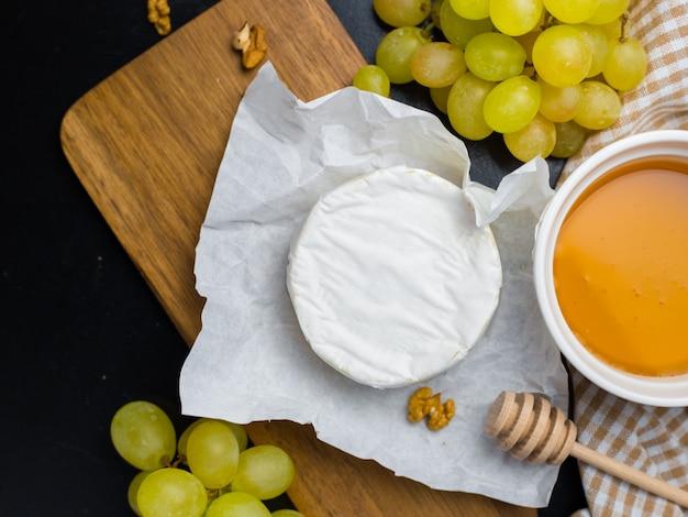 Weichkäse. camembert, honig und trauben auf einem holz mit nüssen.