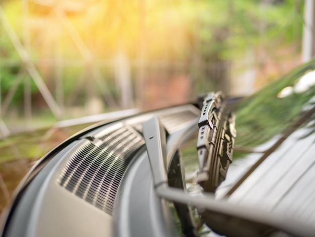 Weichzeichnung am wischer auf dem vorderen spiegel des braunen autos.