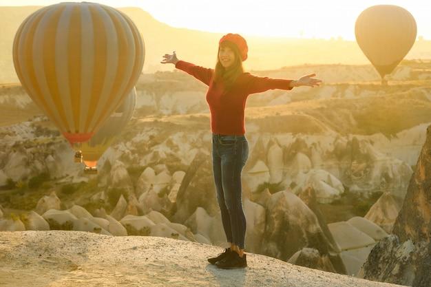 Weichzeichnung auf der asiatischen frau, die auf fantastischer landschaft mit heißluftballonen bei cappadocia, türkisch steht