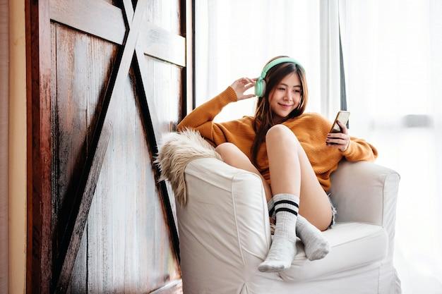 Weichzeichnung der glücklichen jungen frau, die durch musik-kopfhörer im haus sich entspannt