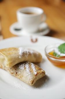 Weichzeichnungsfoto von pfannkuchen mit stau und tasse kaffee.