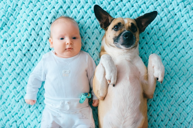 Weichzeichnungsporträt des neugeborenen babylebensstils, das an zurück zusammen mit lustigem welpen auf tadellosem woolen plaid liegt.