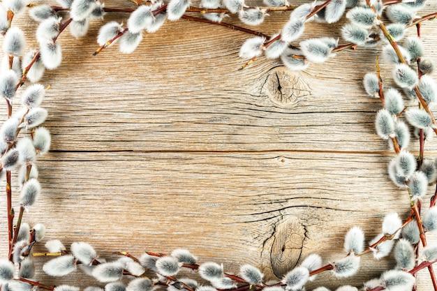 Weidenkätzchen gestalten auf rustikalem strukturiertem hölzernem hintergrund
