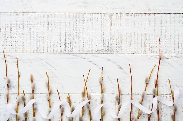 Weidenkätzchenzweige auf weißem altem holztisch. flach liegen.