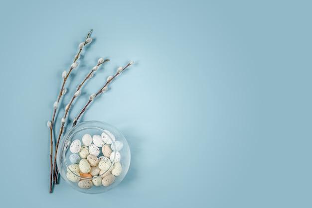 Weidenkätzchenzweige und bunte ostereier im vogelnest auf blauem hintergrund mit kopienraum
