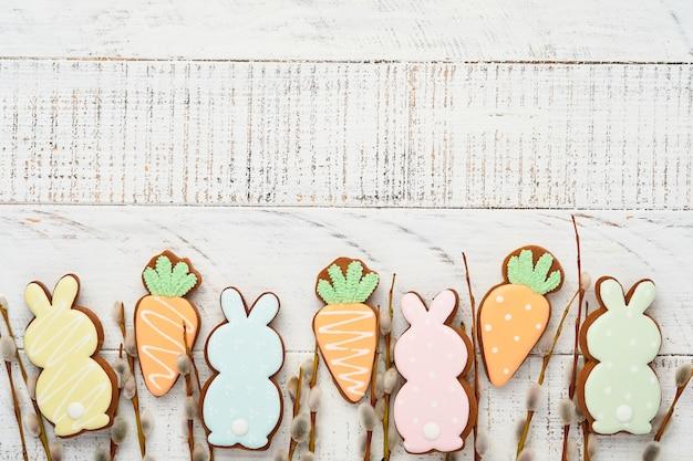 Weidenkätzchenzweige und buntes oster-lebkuchen-kaninchen, eier und hühner auf weißem altem holztisch. festliches osterkonzept. flach liegen.