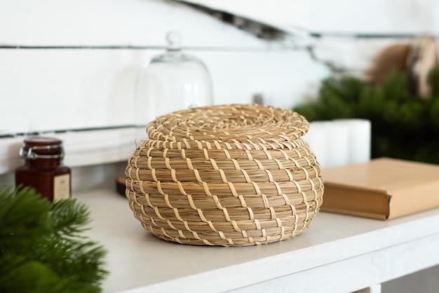 Weidenkorb aus weinstock, auf einem schrank im innenraum. umweltfreundlich, natürliche materialien, umweltfreundlich. boho-stil.