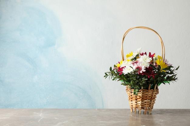 Weidenkorb mit blumen auf grauem tisch gegen blau