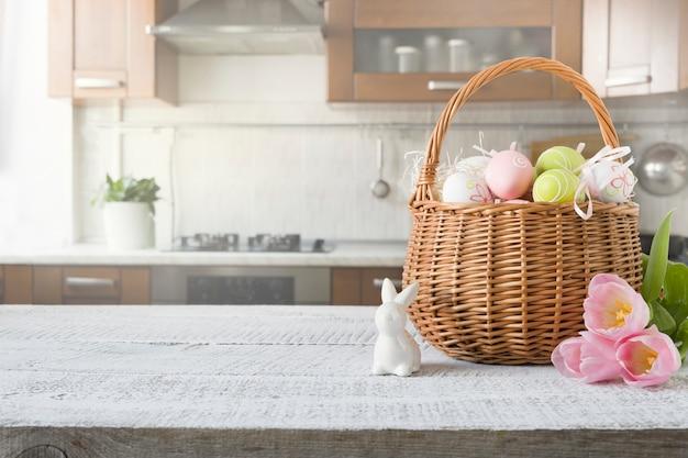 Weidenkorb mit bunten eiern des häschens, der tulpe, des osters auf dem holztisch der küche. frühlings-osterkomposition.