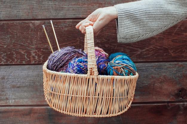 Weidenkorb mit bunten hellen kugeln aus wollgarn zum stricken in weiblichen händen. strickgarn, nadeln, garnstränge. schöne farben zum stricken. konzept handgemachtes kreatives stricken.