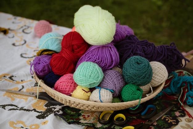 Weidenkorb mit bunten knäueln aus wollgarn zum stricken