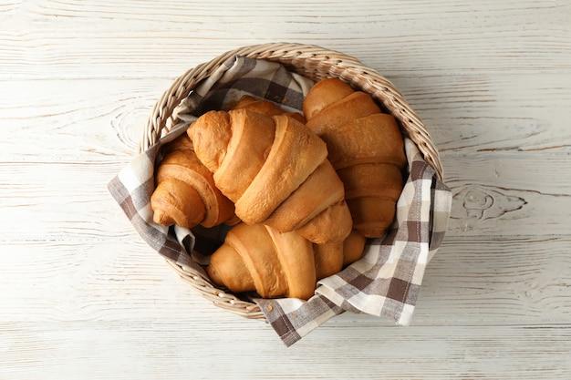 Weidenkorb mit croissants auf holztisch, draufsicht
