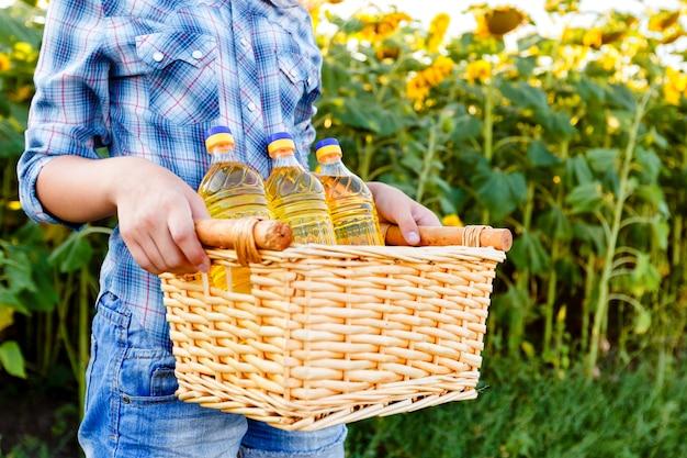 Weidenkorb mit drei flaschen sonnenblumenöl in den weiblichen händen.