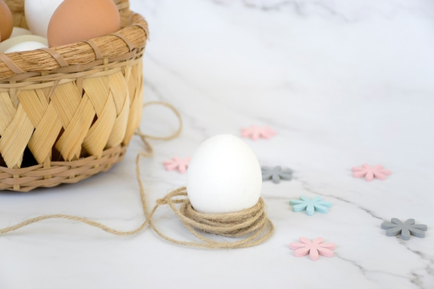 Weidenkorb mit eiern und einzelnem weißem ei im seil mit bunten blumen auf marmorhintergrund. frohe ostern.