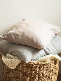 Weidenkorb mit einer weißen weichen gestrickten decke und grauen kissen gegen eine weiße wand