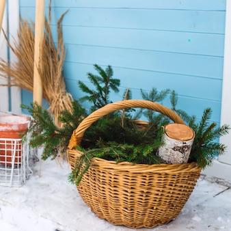 Weidenkorb mit fichtenzweigen neben birkenholz und gartengeräten an der wand des landhauses