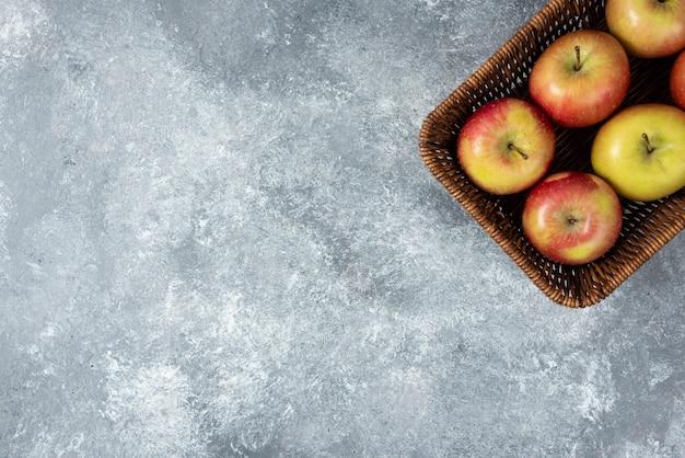 Weidenkorb mit frischen saftigen äpfeln auf marmoroberfläche.