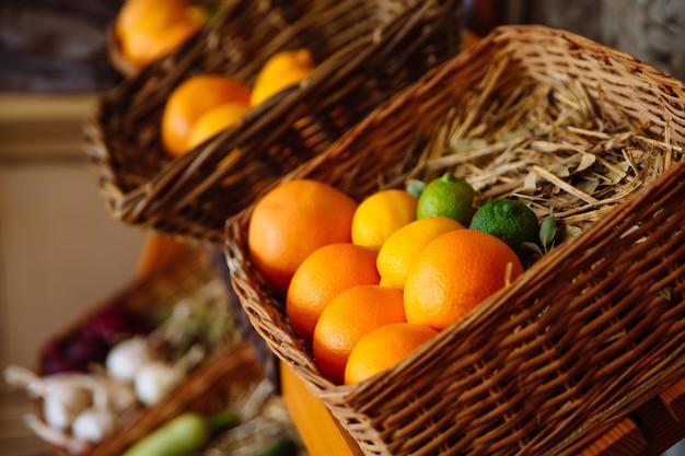 Weidenkorb mit frischen und aromatischen früchten. am boden des korbs liegen stroh und lorbeerblatt. obstkörbe stehen in einer reihe.