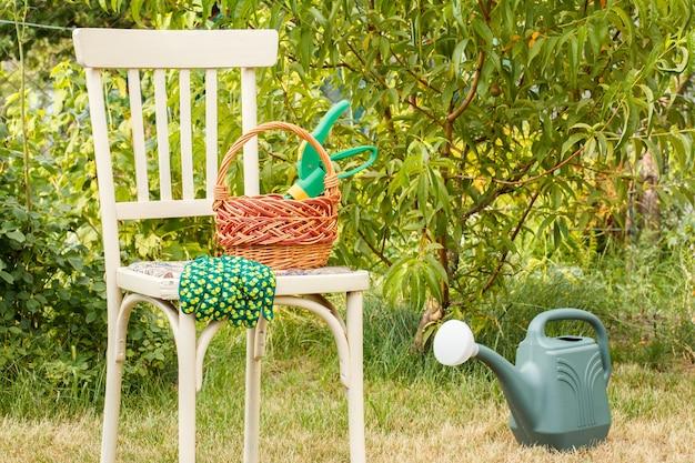 Weidenkorb mit gartenschere und handschuhen auf altem stuhl, gießkanne auf gras im natürlichen hintergrund. gartenwerkzeuge.