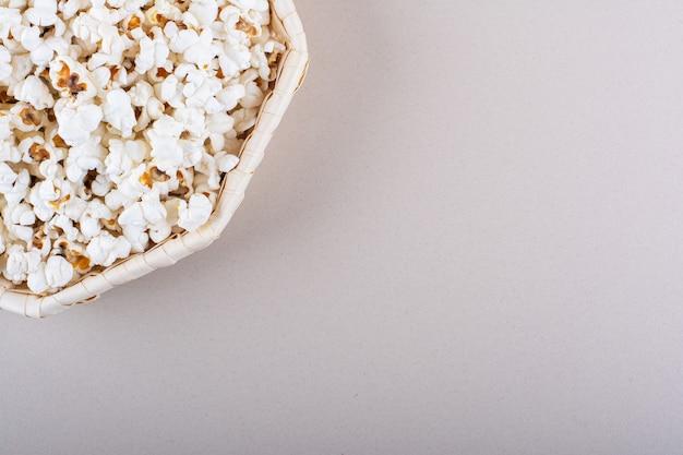 Weidenkorb mit gesalzenem popcorn für den filmabend auf weißem hintergrund. foto in hoher qualität