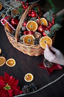 Weidenkorb mit gestreiften zuckerstangen, getrockneten orangenscheiben, zapfen und geschenken.