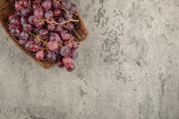 Weidenkorb mit köstlichen roten trauben auf marmortisch.