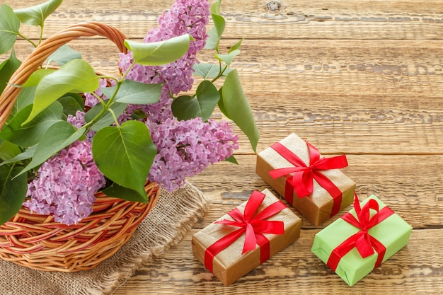 Weidenkorb mit lila blüten und grünen blättern, geschenkboxen mit bändern auf alten holzbrettern. ansicht von oben.