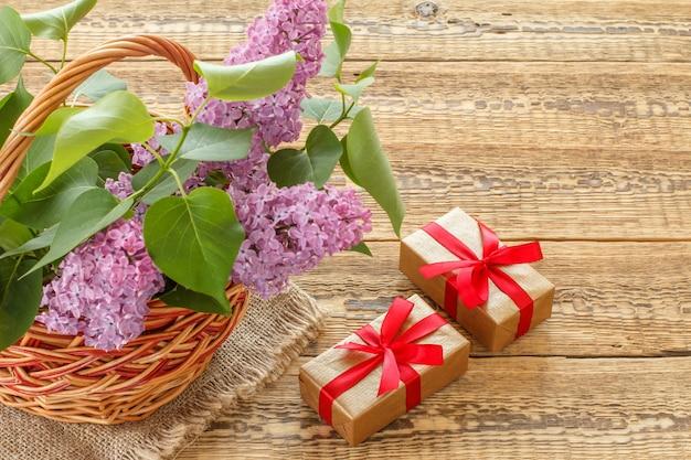 Weidenkorb mit lila blumen und geschenkboxen auf alten holzbrettern. ansicht von oben.