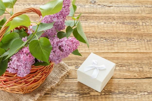 Weidenkorb mit lila blumen und weißer geschenkbox auf holzbrettern. draufsicht mit kopienraum.